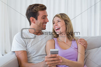 Cheerful couple text messaging on couch