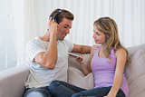 Couple listening music with mobile phone on couch