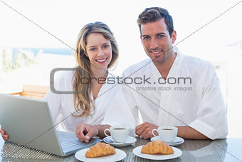 Couple using laptop on breakfast table