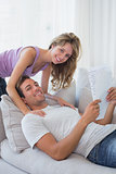 Relaxed young couple reading document on couch