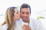 Woman kissing man while having coffee