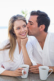 Man kissing woman while having coffee