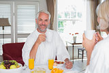 Happy mature man with woman having breakfast