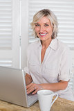 Smiling casual mature woman using laptop at home