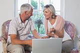 Couple discussing while using laptop at home