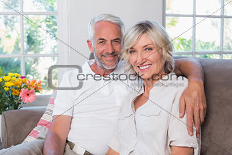 Smiling mature couple sitting on sofa in living room