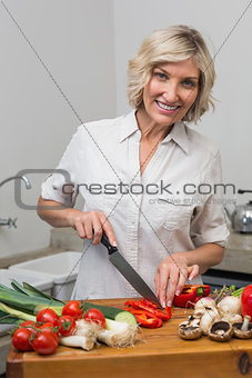 Mature woman chopping vegetables in kitchen