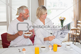 Couple reading newspaper while having breakfast