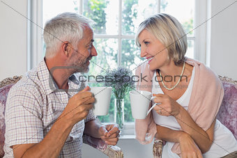 Mature couple with coffee cups at home
