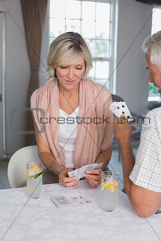 Mature couple playing cards at home