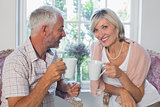 Smiling mature couple with coffee cups