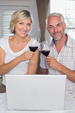 Happy mature couple toasting wine glasses at home