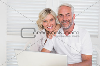 Portrait of mature couple using laptop at home