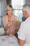 Mature couple toasting drinks while playing cards at home