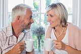 Smiling mature couple with coffee cups at home
