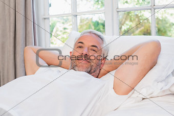 Relaxed mature man lying in bed at home