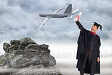 Composite image of delighted boy celebrating his graduation
