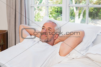 Thoughtful mature man lying in bed