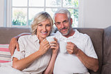 Smiling mature couple with coffee cups in living room