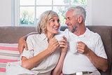 Relaxed mature couple with coffee cups in living room