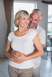 Mature man embracing woman at home
