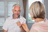 Smiling mature man playing cards with woman at home