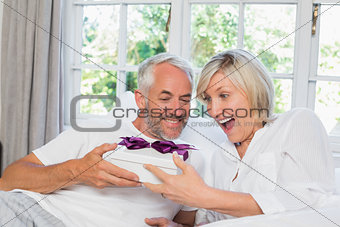 Mature man giving surprised woman gift box at home