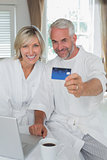 Mature couple holding out credit card at home
