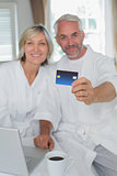 Happy mature couple holding out credit card at home
