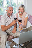 Mature couple with wine glasses using laptop