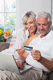Happy mature couple doing online shopping at home