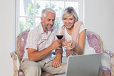 Mature couple with wine glass using laptop at home