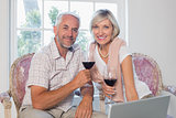 Relaxed mature couple with wine glass using laptop