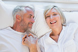 High angle portrait of mature couple lying in bed