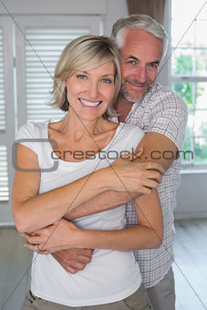 Mature man embracing woman from behind