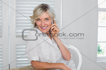 Mature woman using mobile phone at home