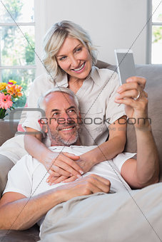 Mature couple photographing themselves with cellphone