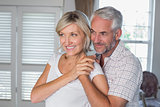 Smiling mature man embracing woman