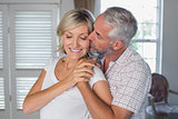 Mature man kissing a happy woman