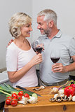 Loving mature couple with wine glasses in kitchen