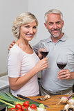 Mature couple with wine glasses in kitchen