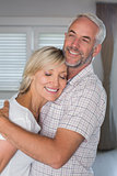Mature couple embracing at home