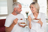 Loving mature couple having breakfast at home