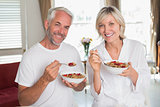 Happy mature couple having breakfast at home