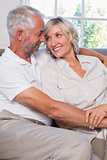 Mature couple looking at each other in living room