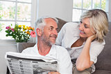 Couple looking at each other while reading newspaper