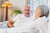 Smiling relaxed mature couple lying in bed