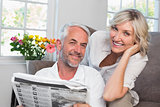 Happy mature couple reading newspaper at home