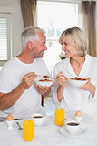 Couple looking at each other and having breakfast