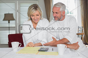 Cature couple sitting with home bills and calculator